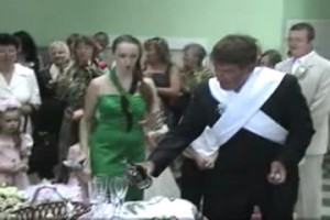 The druzhba opens a bottle of champagne and pours it into the glasses for the newlyweds and their parents.